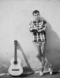 Stattlicher schauender junger Mann der Gitarre Stockfotografie