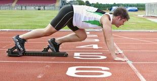 Stattlicher Sprinter auf der Anfangszeile im Stadion Lizenzfreie Stockbilder