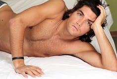 Stattlicher und reizvoller junger Mann auf Bett Lizenzfreies Stockbild