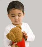 Stattliches Kleinkind, das mit einem Teddybären spielt Lizenzfreie Stockfotos