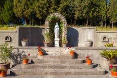 Statua święci martyress w kościelnym ` s cortyard z kwiatami Obrazy Royalty Free