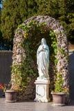 Statua święci martyress w kościelnym ` s cortyard z kwiatami Zdjęcia Stock