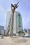 Statua alta con l'edificio per uffici sul fondo, Yantai, Cina Fotografie Stock