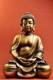 Statua Bronze del Buddha contro priorità bassa arancione rossa Immagine Stock