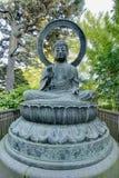 Statua Bronze del Buddha in giardino giapponese Immagini Stock