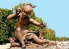 Statua bronzea di una bambina che sente il suono di una conca e fotografia stock libera da diritti