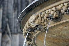 Statua brutta del demone con il flusso continuo dell'acqua dalla bocca vicino a Colonia c immagini stock libere da diritti