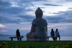 Statua Buddha i trzy twój kobiety ogląda zmierzch nad oceanem spokojnym zdjęcie stock