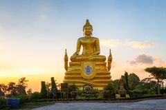 Statua d'ottone di Buddha vicino al grande Buddha nel tramonto fotografia stock