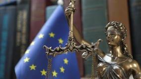 Statua damy sprawiedliwość z półką na książki z książek i UE flagi tłem zbiory wideo