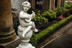 Statua del cupido che gioca la chitarra immagini stock