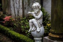 Statua del cupido che gioca la flauto Immagine Stock Libera da Diritti