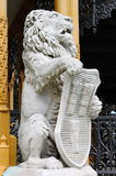 Statua del leone con lo schermo Fotografie Stock Libere da Diritti
