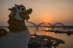 Statua del leone vicino al ponte di Yadanarbon al tramonto sopra Ayeyarwady Riv immagine stock