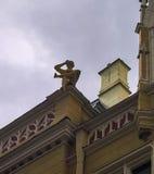 Statua del ragazzo sul tetto della casa, Riga, Lettonia della lettura Fotografia Stock