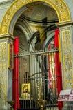 Statua della crocifissione di Jesus Christ fra le icone all'altare su cui è l'ombra riflessa sulla parete del tempio nella t Immagini Stock