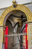 Statua della crocifissione di Jesus Christ fra le icone all'altare su cui è l'ombra riflessa sulla parete del tempio nella t Fotografia Stock