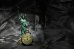 Statua della libertà con l'orologio da tasca d'annata sul fondo nero del tessuto Ancora studio di vita photography Immagine Stock