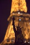 Statua della libertà sui precedenti della torre Eiffel di sera Immagine Stock Libera da Diritti