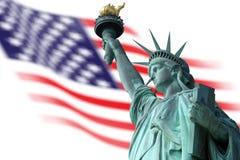 Statua della libertà sull'isola a New York con la bandiera Fotografia Stock