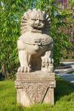 Statua della pietra del leone del guardiano sul piedistallo in un parco Immagini Stock