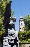 Statua di angelo con la torre di chiesa sull'isola/Germania di Mainau fotografia stock