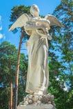 Statua di angelo con le ali sui precedenti del cielo Fotografia Stock