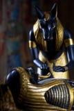Statua di Anubis con la mummia del deceduto su un backg nero immagini stock libere da diritti