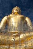 Statua di Buddha dell'oro in costruzione in tempio tailandese con il chiaro cielo WAT MUANG, Ang Thong, TAILANDIA Immagine Stock