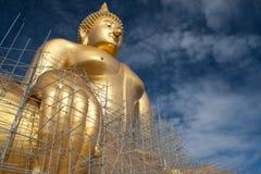 Statua di Buddha dell'oro in costruzione in tempio tailandese con il chiaro cielo WAT MUANG, Ang Thong, TAILANDIA Immagine Stock Libera da Diritti