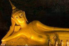Statua di Buddha dorato adagiantesi in caverna Fotografia Stock Libera da Diritti