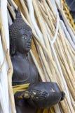Statua di Buddha nel gruppo di legno del ramo Immagini Stock