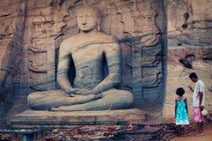 Statua di Buddha scolpita nella roccia immagine stock