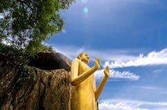 Statua di Buddha sulla montagna e sull'albero e bello cielo blu nel luogo pubblico Immagini Stock
