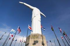 Statua di Cristo del Rey di Cali con le bandiere del mondo ed il cielo blu, passo Fotografia Stock