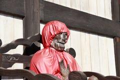 Statua di legno di Buddha di Yakushi Nyorai in cappuccio rosso, Buddha di medicina e di salute fotografia stock