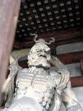 Statua di legno impressionante all'entrata ad un tempio giapponese fotografia stock