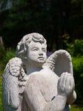Statua di pietra di angelo che prega e che guarda verso il cielo Fotografia Stock