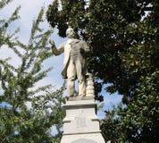 Statua di pietra di un uomo ben vestito con una pila di libri Immagini Stock