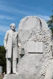 Statua di pietra di un uomo ben vestito con una pila di libri Fotografia Stock Libera da Diritti