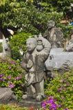 Statua di poca ragazza cinese con un monaco in giardino verde. Immagine Stock
