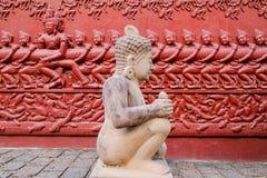 Statua di scultura di pietra con una scultura sulla parete dietro immagine stock