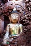 Statua di seduta antica di Buddha in vestiti dell'oro vicino su in una delle tempie di Bagan nel Myanmar fotografia stock