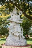 Statua di sohei di Buddha del guerriero del monumento della statua con il fondo verde degli alberi con i fiori gialli fotografia stock
