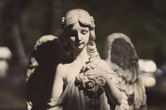 Statua di un angelo con le ali nel sole Fotografia Stock