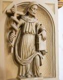 Statua di un san che tiene un incrocio con un serpente nella cattedra fotografia stock