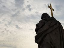 Statua di un san con un incrocio, cielo come fondo Immagini Stock Libere da Diritti