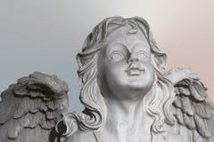Statua di una pietra bianca che prega angelo su backgrouond, sul fronte e sulle ali pastelli immagine stock libera da diritti