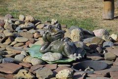 Statua di una rana su una ninfea Una statua sui ciottoli fotografia stock