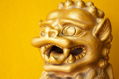 Statua dorata cinese di Leo su fondo giallo bianco Immagine Stock